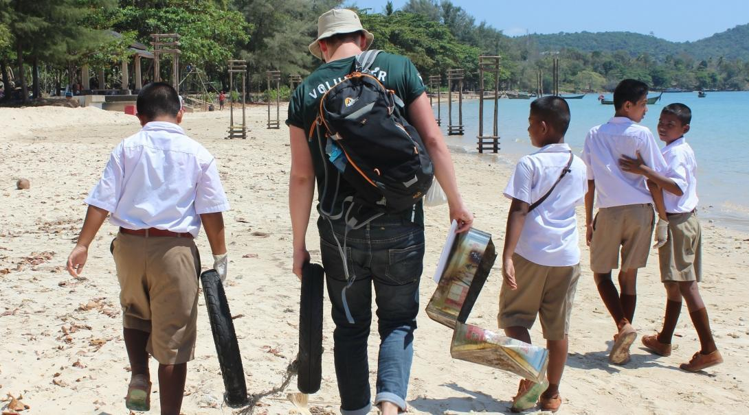 A high school student volunteer picks up litter on the beach to promote marine conservation in Thailand